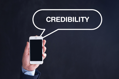 credibility: Hand Holding Smartphone with CREDIBILITY written speech bubble