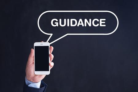 guidance: Hand Holding Smartphone with GUIDANCE written speech bubble Stock Photo