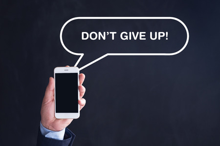 committed: Hand Holding Smartphone with DONT GIVE UP! written speech bubble