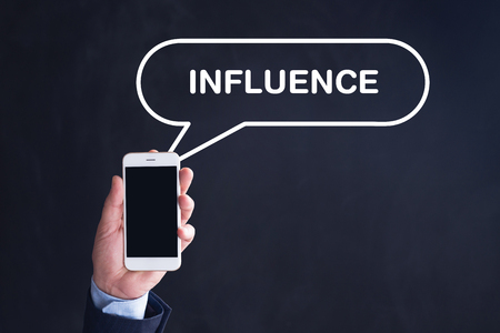influencer: Hand Holding Smartphone with INFLUENCE written speech bubble Stock Photo