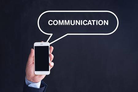 comunicación escrita: Mano que sostiene el teléfono inteligente con la comunicación escrita burbuja del discurso