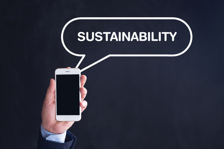 sustain: Hand Holding Smartphone with SUSTAINABILITY written speech bubble