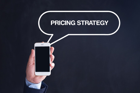 pricing: Hand Holding Smartphone with PRICING STRATEGY written speech bubble