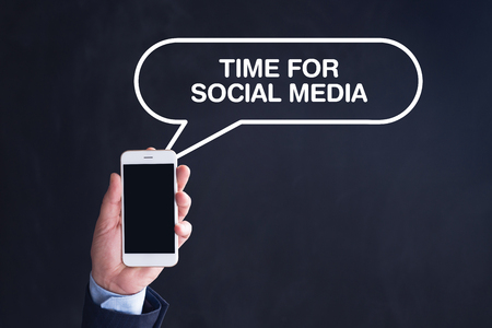 textcloud: Hand Holding Smartphone with TIME FOR SOCIAL MEDIA written speech bubble