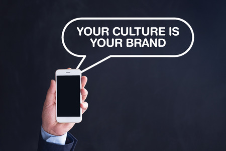 Hand Holding Smartphone with YOUR CULTURE IS YOUR BRAND written speech bubble