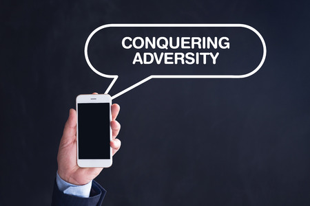 adversity: Hand Holding Smartphone with CONQUERING ADVERSITY written speech bubble