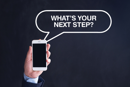 what's ahead: Hand Holding Smartphone with WHATS YOUR NEXT STEP? written speech bubble