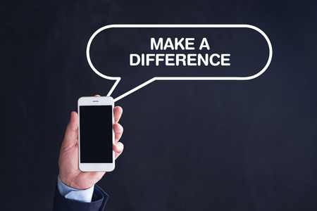 Hand Holding Smartphone with MAKE A DIFFERENCE written speech bubble