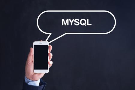 mysql: Hand Holding Smartphone with MYSQL written speech bubble Stock Photo