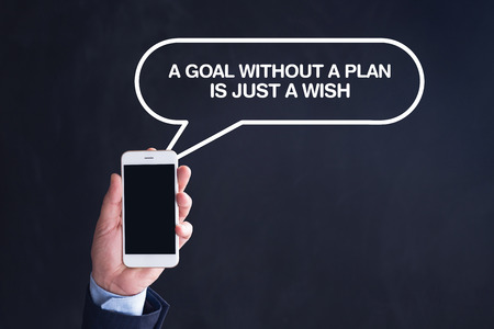 strategic focus: Hand Holding Smartphone with A GOAL WITHOUT A PLAN IS JUST A WISH written speech bubble Stock Photo