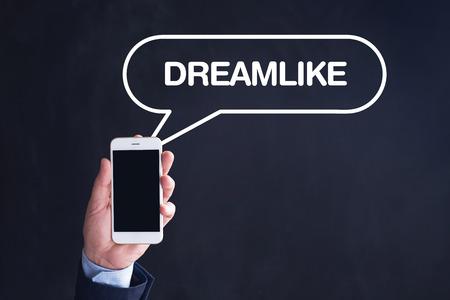 dreamlike: Hand Holding Smartphone with DREAMLIKE written speech bubble