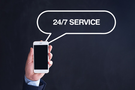 24x7: Hand Holding Smartphone with 247 SERVICE written speech bubble Stock Photo