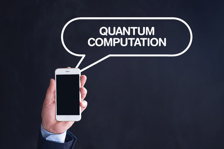 computation: Hand Holding Smartphone with QUANTUM COMPUTATION written speech bubble Stock Photo