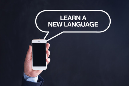 fluency: Hand Holding Smartphone with LEARN A NEW LANGUAGE written speech bubble Stock Photo