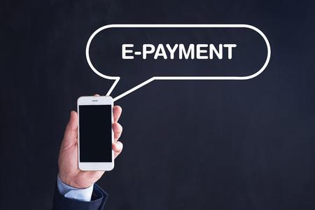 epayment: Hand Holding Smartphone with E-PAYMENT written speech bubble