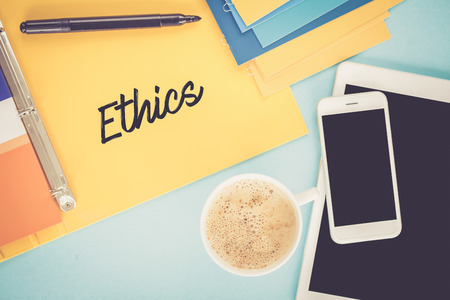 work ethic responsibilities: Notepad on workplace table and written ETHICS concept Stock Photo