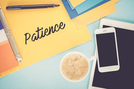 paciencia: Bloc de notas en la mesa de trabajo y Concepto de la paciencia por escrito