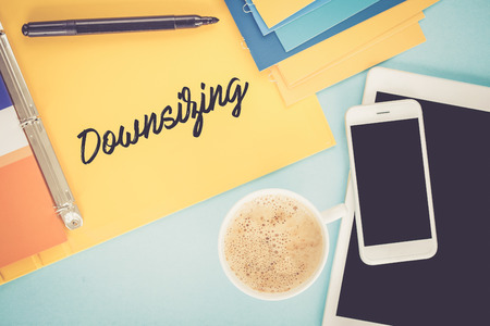 downsizing: Notepad on workplace table and written DOWNSIZING concept