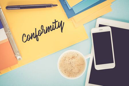 conformity: Notepad on workplace table and written CONFORMITY concept