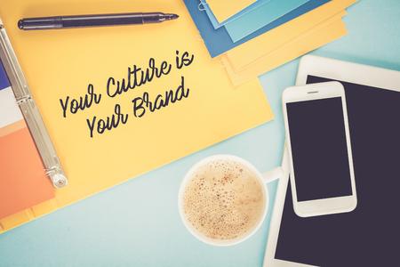 Bloc de notas en la mesa de trabajo y escrita SU CULTURA ES SU concepto de marca