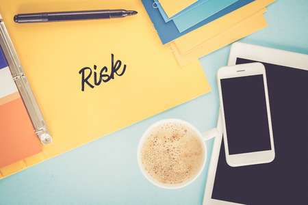 risky situation: Notepad on workplace table and written RISK concept Stock Photo