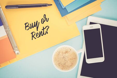 buying questions: Notepad on workplace table and written BUY OR RENT? concept