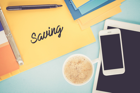 frugality: Notepad on workplace table and written SAVING concept