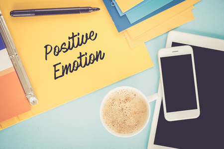synonym: Notepad on workplace table and written POSITIVE EMOTION concept