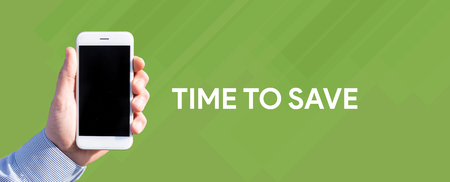 frugality: Smart phone in hand front of green background and written TIME TO SAVE Stock Photo