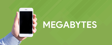 megabytes: Smart phone in hand front of green background and written MEGABYTES