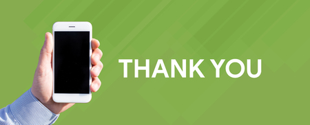 Smart phone in hand front of green background and written THANK YOU