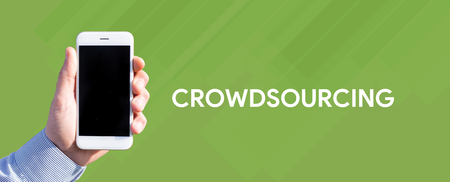 crowd source: Smart phone in hand front of green background and written CROWDSOURCING Stock Photo