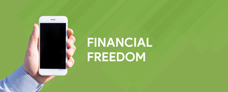 conservative: Smart phone in hand front of green background and written FINANCIAL FREEDOM