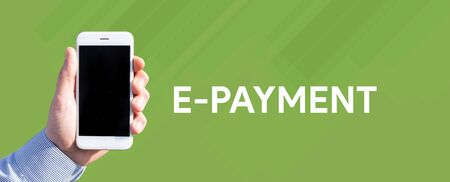epayment: Smart phone in hand front of green background and written E-PAYMENT