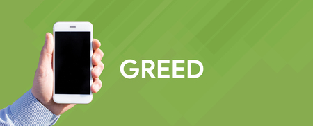 avid: Smart phone in hand front of green background and written GREED