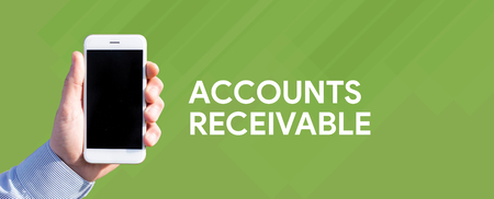 chit: Smart phone in hand front of green background and written ACCOUNTS RECEIVABLE Stock Photo