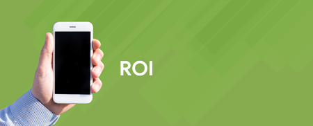 Smart phone in hand front of green background and written ROI