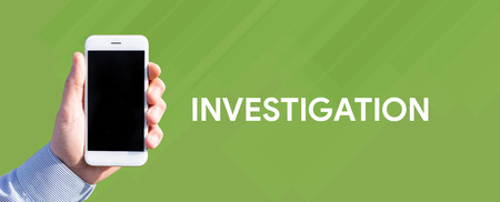 Smart phone in hand front of green background and written INVESTIGATION Stock Photo