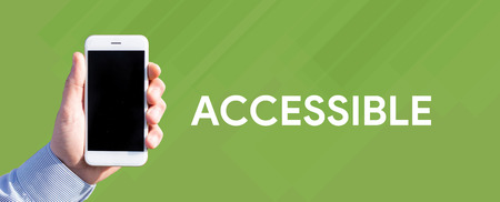 availability: Smart phone in hand front of green background and written ACCESSIBLE Stock Photo