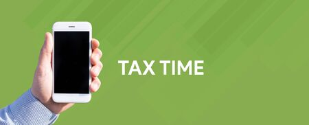rate of return: Smart phone in hand front of green background and written TAX TIME Stock Photo