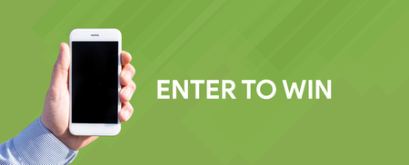 Smart phone in hand front of green background and written ENTER TO WIN Stock Photo
