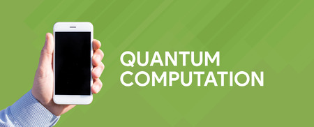 computation: Smart phone in hand front of green background and written QUANTUM COMPUTATION
