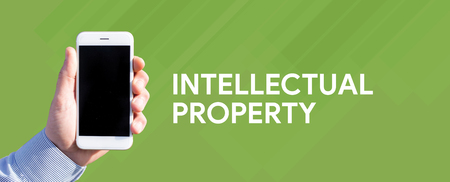 Smart phone in hand front of green background and written INTELLECTUAL PROPERTY
