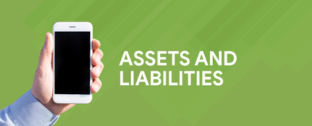 Smart phone in hand front of green background and written ASSETS AND LIABILITIES