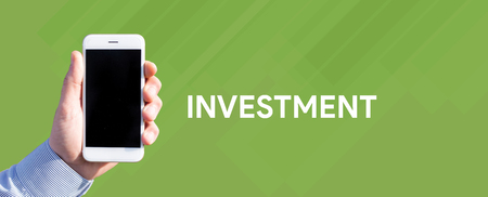 Smart phone in hand front of green background and written INVESTMENT Stock Photo
