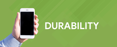durability: Smart phone in hand front of green background and written DURABILITY