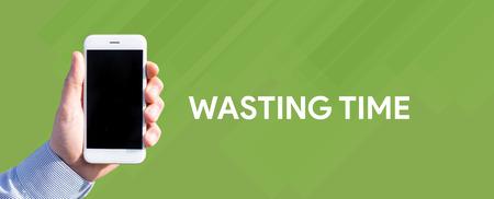 cronologia: Teléfono inteligente en frente de la mano de fondo verde y escrito TIEMPO DE DESPERDICIO