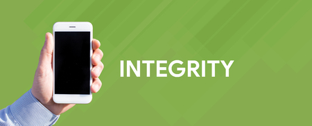 Smart phone in hand front of green background and written INTEGRITY Stock Photo