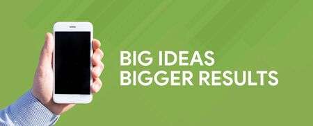bigger: Smart phone in hand front of green background and written BIG IDEAS BIGGER RESULTS Stock Photo