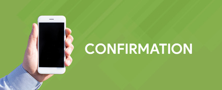 Smart phone in hand front of green background and written CONFIRMATION Stock Photo